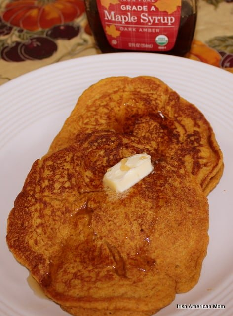 Pumpkin Pancakes on a white plate beside a bottle of maple syrup