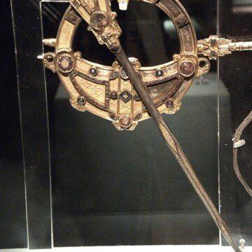 Golden Celtic brooch on display in a museum display case