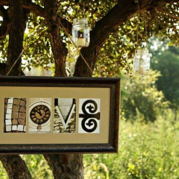 Framed artwork spelling LOVE hanging from a tree branch