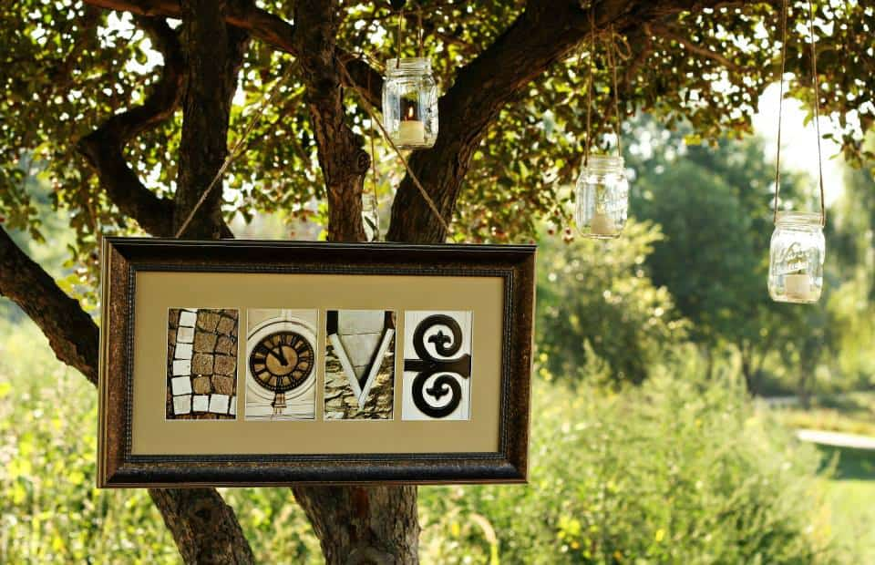 Framed artwork spelling LOVE hanging from a tree branch
