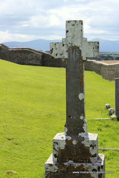graveyard cross in a walled green field