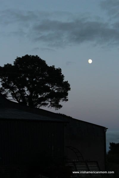 A full moon in the twilight sky over an Irish barn