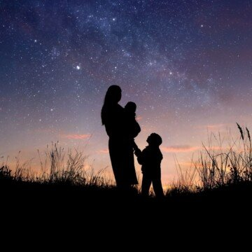 A woman and two children in silhouette against a starry twilight sky