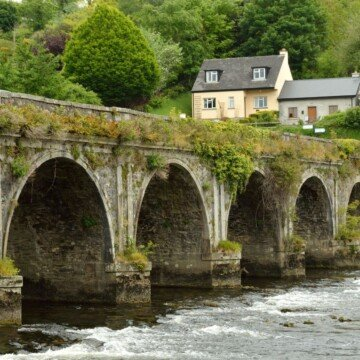 Arched bridge over a river beside two stone cottages