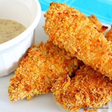 golden crispy chicken tenders beside honey mustard sauce