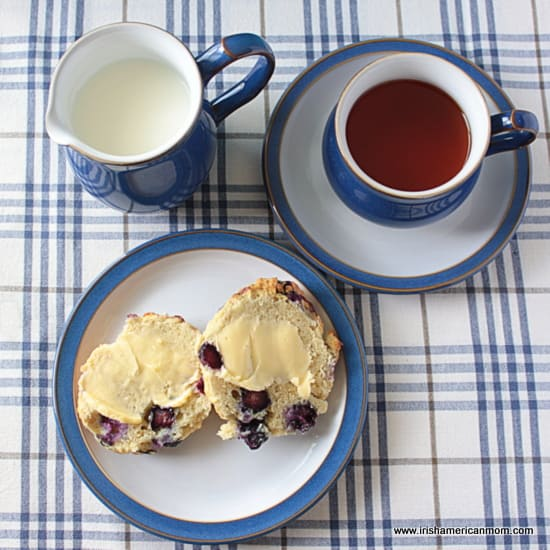 a cup of tea with a milk jug and a buttered blueberry scone