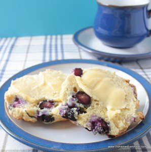 Buttered halves of a blueberry scone with a tea cup