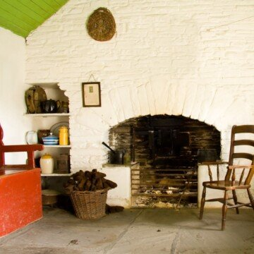 An open hearth with a chair and a bucket of turf