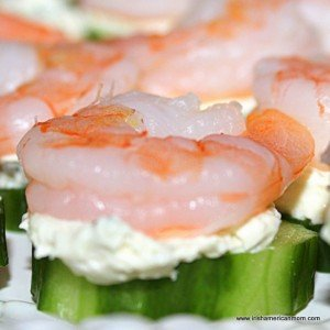 Shrimp on a cream cheese layer on top of a slice of cucumber