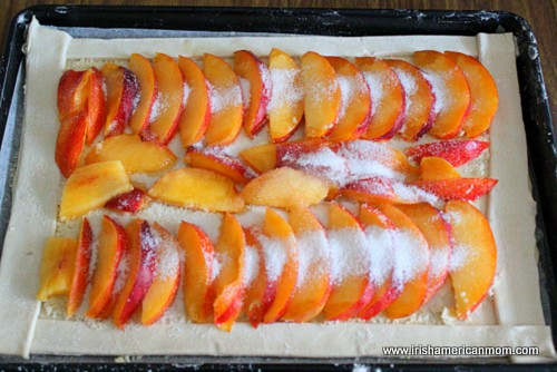 Sprinkling sugar on sliced nectarines for a galette