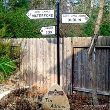 Irish style black and white road sign as a piece of art in a garden