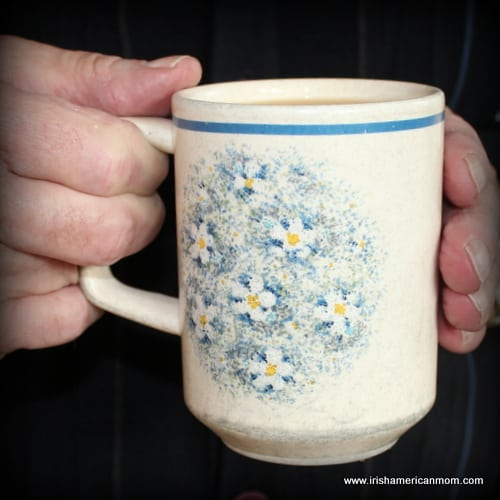 A floral mug held in a man's hands