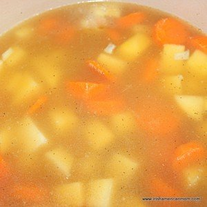 Chicken or vegetable broth added to carrots and rutabaga for a soup recipe