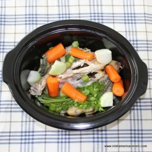 Chicken carcass with vegetables in a crock pot for homemade chicken stock