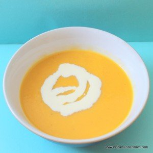 Cream poured on top of a bowl of carrot and rutabaga soup