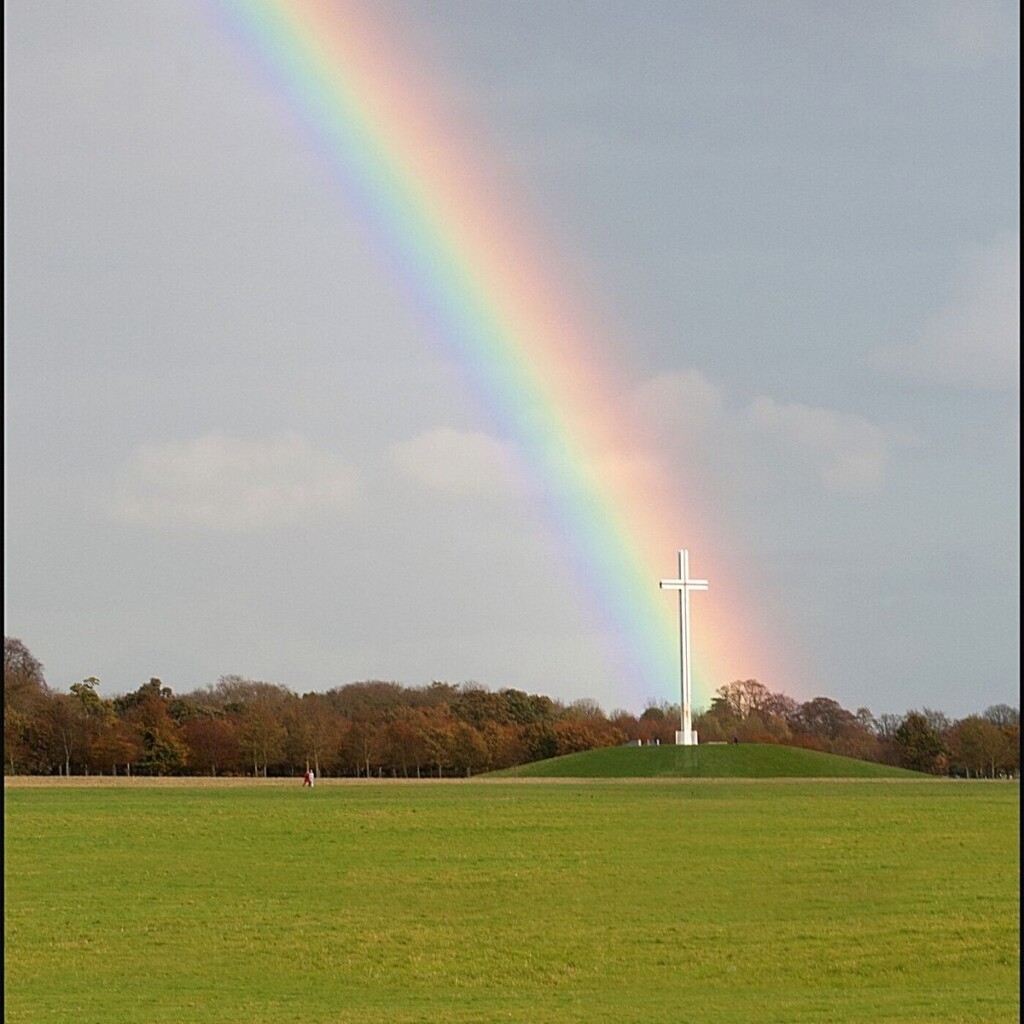 A rainbow falling on a white cross in a green field