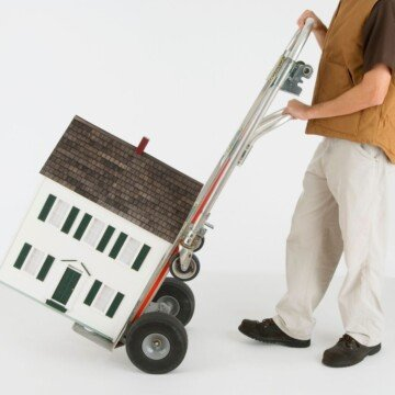 A man pushes a dolly holding a model of a house