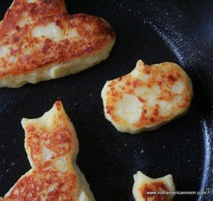 A cat and witch hat potato cake frying in a pan