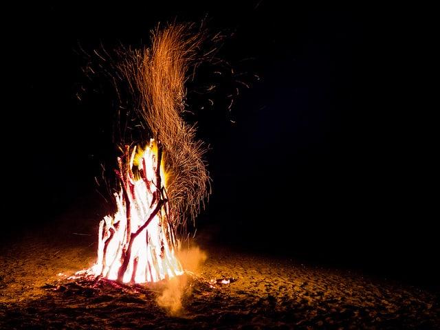 Bonfire sending sparks into a black sky