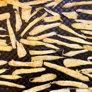 Seasoned uncooked parsnip chips on a baking tray