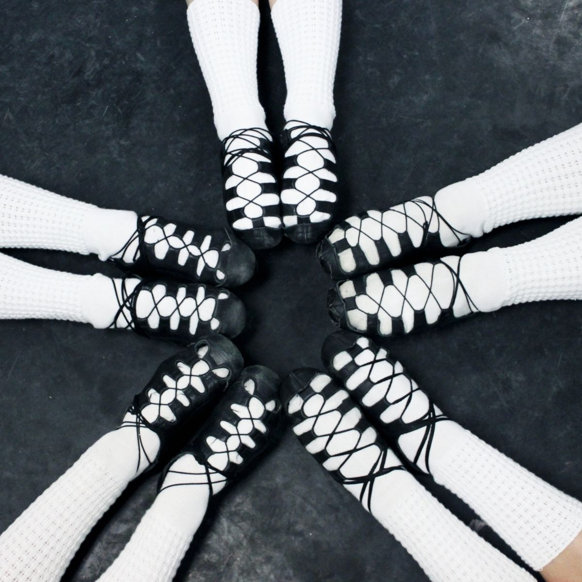Five pairs of legs with white socks and Irish soft dance shoes in a circle