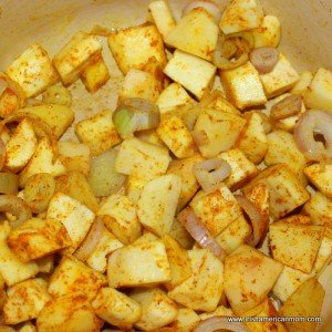 Parsnips and shallots sweating with curry powder in a Dutch oven for parsnip and apple soup