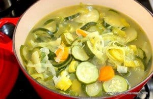 Leeks and vegetable simmering in a Dutch oven for zucchini and leek soup