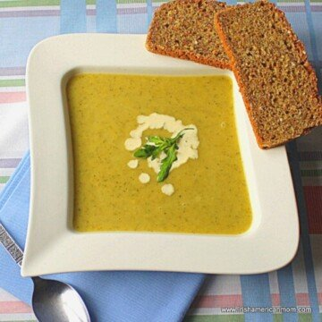 Soup in a square bowl with two slices of bread balanced on the edge