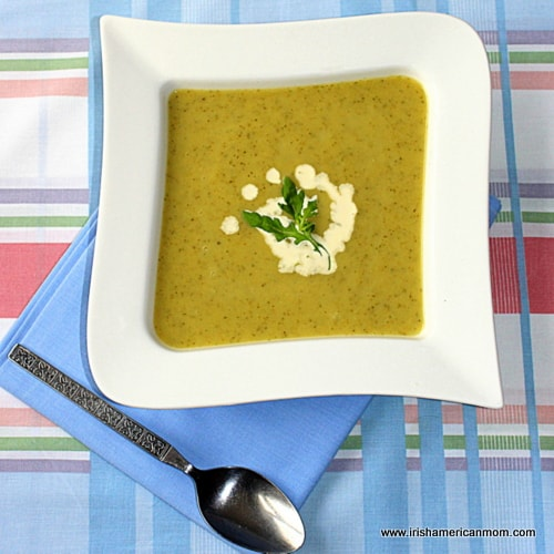 A bowl of zucchini and leek soup with cream to garnish