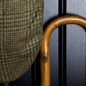 A tweed cap beside a wooden cane