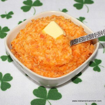 A bowl of carrot and parsnip mash on a shamrock cloth