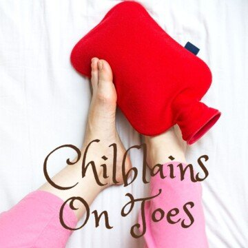 Feet holding a red hot water bottle with text overlay