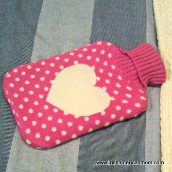 Pink polka dot hot water bottle cover with a white heart