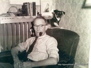 A black and white photo of a man with his dog on the back of his armchair