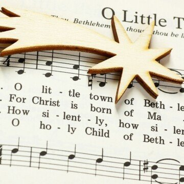 A music score with clefs and text and a golden star laid on top of it