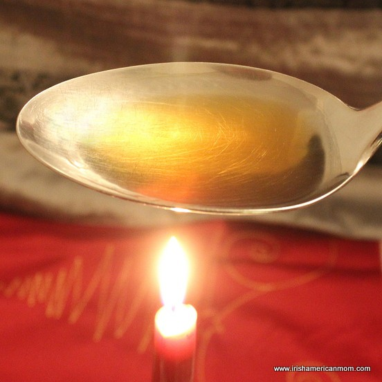 A metal spoonful of brandy over a candle flame