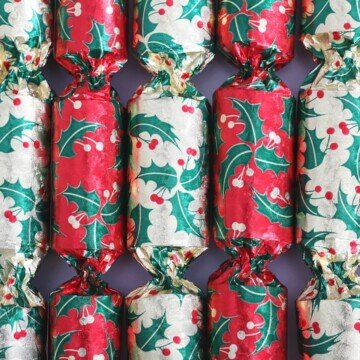 A row of Christmas crackers in greens, reds, and golds.