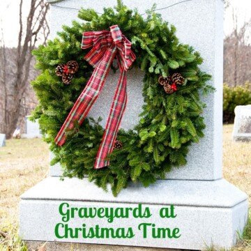 A large green wreath with tartan red bow on a gravestone