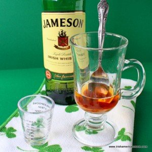 A shot of Jameson whiskey in a glass with a spoon for Irish hot whiskey