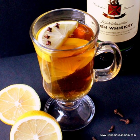 A glass of Irish hot whiskey with a slice of lemon and cloves