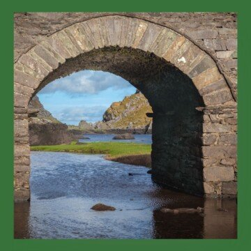 Arched bridge with mountain landscape showing under the archway