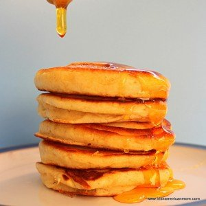 Dripping honey over a stack of drop scones or pocket pancakes