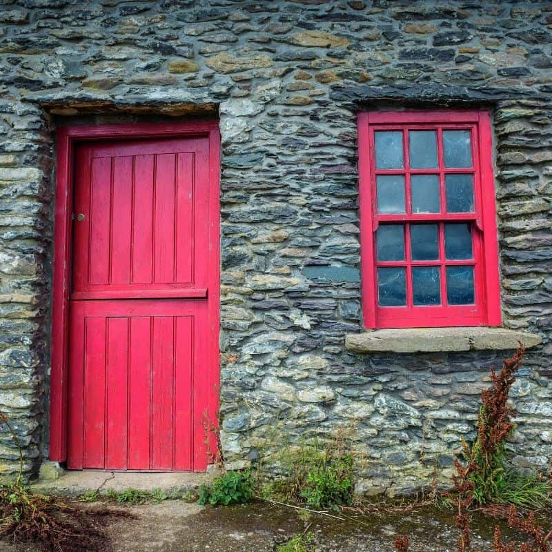 A stone cottage in Ireland with a red half door and a red cottage window