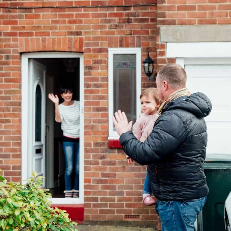 A family waves goodbye to each other at a house door