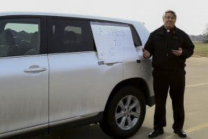 A pastor or priest stands beside his car with a sign Ashes To Go