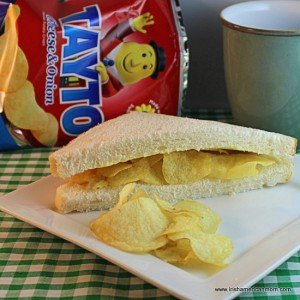 A packet of Tayto beside a plate with a crisp sandwich