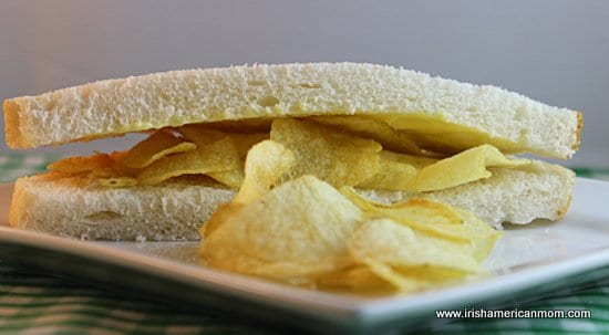 White bread and butter sandwich with cheese and onion crisps