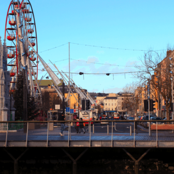 A ferris wheel beside a monument and buildings