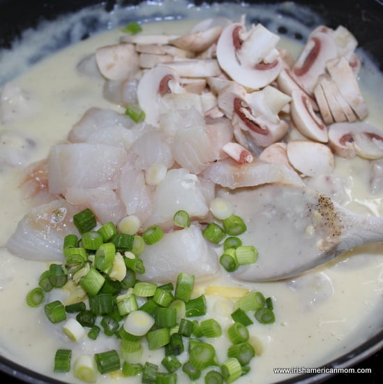 Adding cod, green onions and mushrooms to cheesy seafood bake