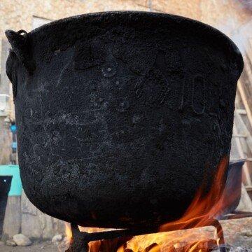 A large cast iron pot on an open fire